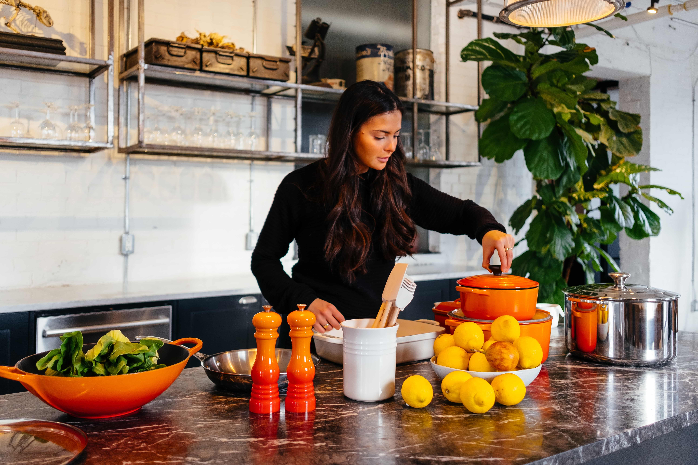 Une femme en train de cuisiner sur un plan de travail en bois
